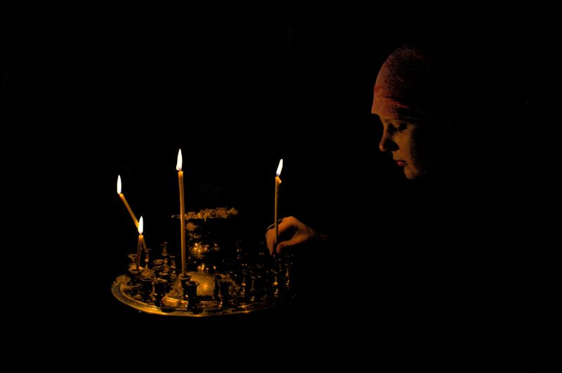 Lighting_a_candle_in_Orthodox_church,_Ukraine